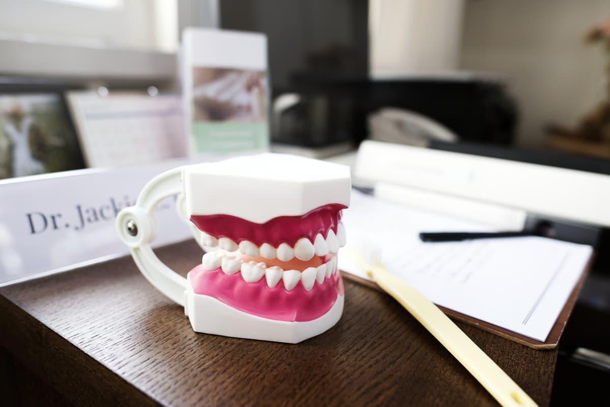 dentures sitting on dentist desk next to paperwork